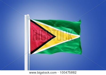 Flag of Guyana flying against a blue sky.