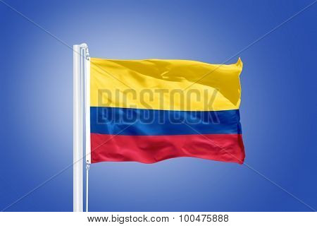 Flag of Colombia flying against a blue sky.