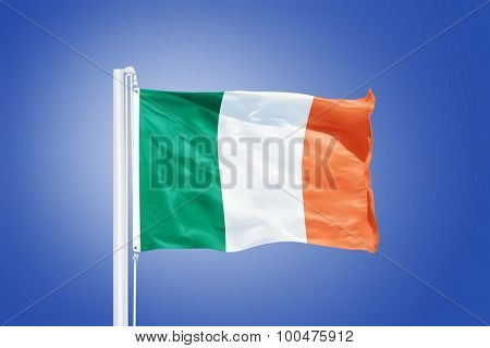 Flag of Ireland flying against a blue sky.