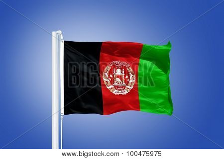 Flag of Afghanistan flying against a blue sky.