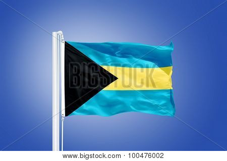 Flag of Bahamas flying against a blue sky.