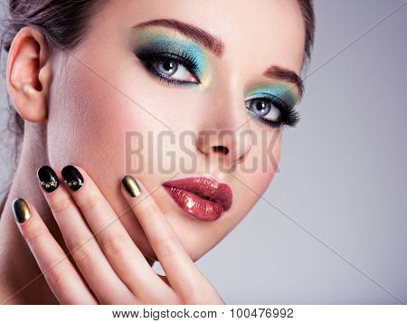 Close-up face of  a Beautiul woman with green creative make-up