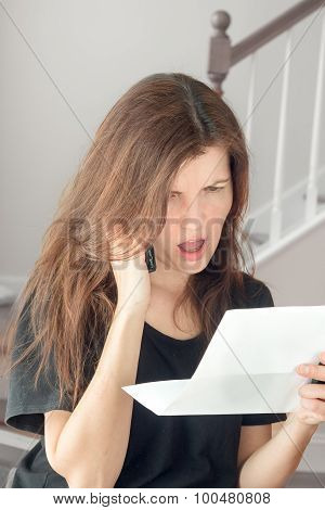 angry woman talking on the phone and looking at correspondence