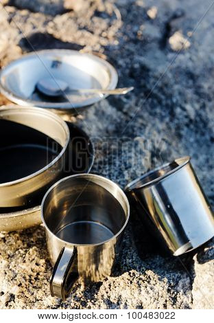 Set of camping cookware pot, bowl, pan, mug and utensils outdoor in the morning sunlight at a remote mountain wilderness campsite