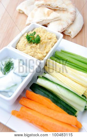 Tzatziki (yoghurt and cucumber) and hummus (chickpea) dips with raw carrot, cucumber, corn and celery with pita or naan bread