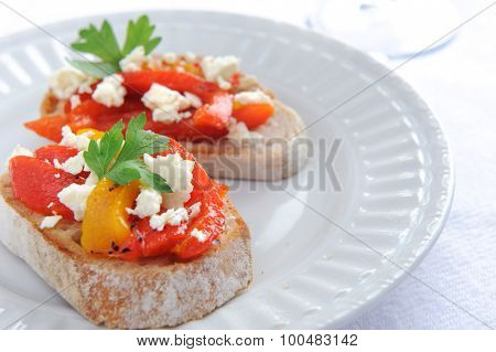 Slices of baguette topped with roasted red and yellow peppers with feta cheese