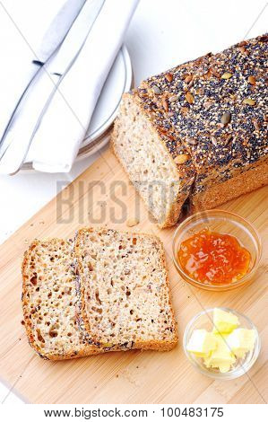 Fresh sliced whole wheat bread with butter and jam, healthy living concept