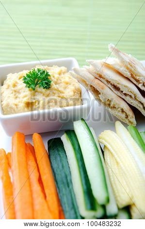 Vegetarian platter of raw carrots, corn, cucumber and celery sticks with chickpea dip and flatbread