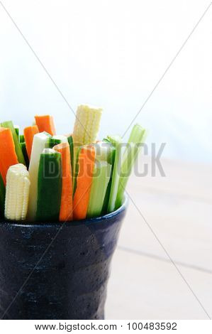 Ready to eat raw sticks of carrot, cucumber, corn and celery in a cup