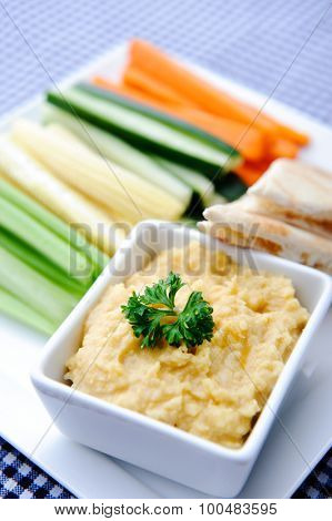Colourful vegetarian platter of raw carrots, corn, cucumber and celery sticks with chickpea dip and flat bread