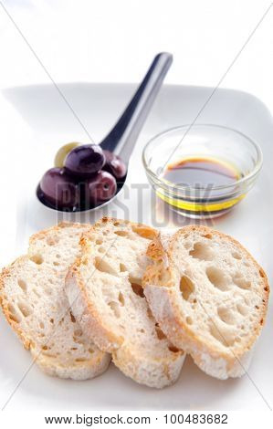 Bread slices with mixed olives and a olive oil and balsamic vinegar dip