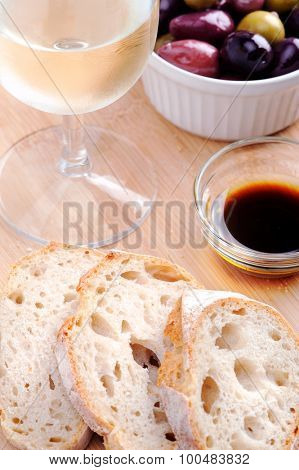 Bread slices with olive oil and balsamic vinegar, glass of wine and a bowl of mixed olives