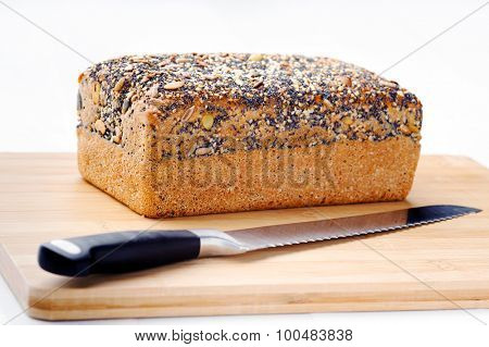 Loaf of healthy whole grain brown bread with a bread knife