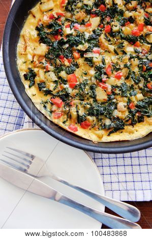 Ready to serve spinach and red bell pepper frittata with serving utensils