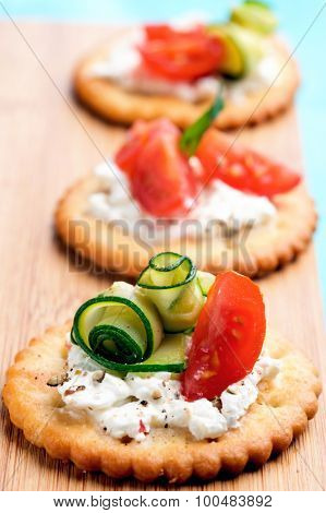 Bite size canapes with ricotta cheese, zucchini and tomato