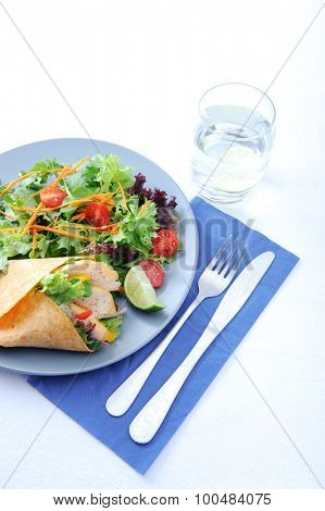 Colorful chicken wrap with plenty of fresh salad and a set of cutlery