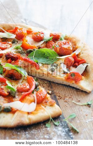 Italian pizza with fresh herbs, roasted tomatoes, peppers, capers and shaved cheese