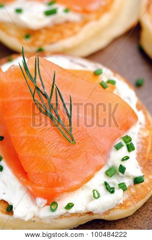 Close up on a smoked salmon appetiser garnished with dill and chives