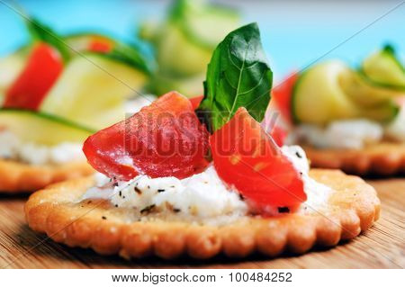 Bite size canapes with ricotta cheese and tomato garnished with basil