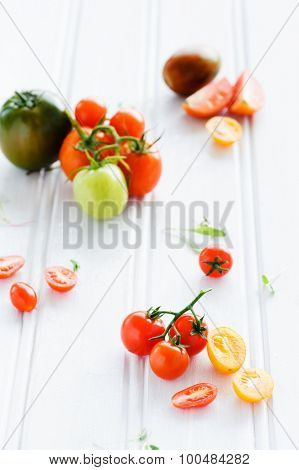 Still life arrangement of cut and whole tomatoes on rustic background with fresh leaves; cherry, roma, green, yellow variety; copy space available