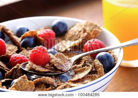 Breakfast cereal with milk and berries and orange juice