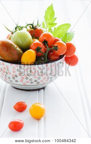 Raw mixed tomatoes in an ornate bowl, cherry, roma, green, yellow, vine ripened with fresh green leaves