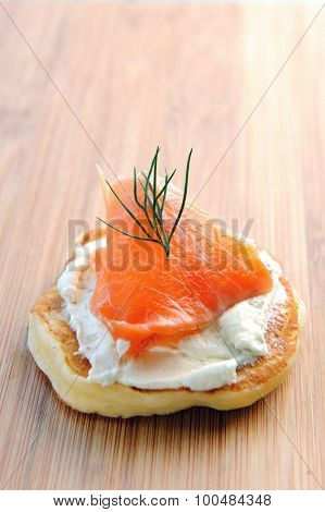 Blini with cream cheese topped with smoked fish and dill on a wooden board