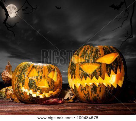 Halloween pumpkins on wood with dark sky background