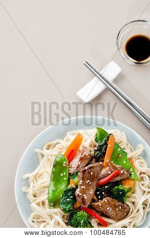 Stir fry beef asian chinese noodles with vegetables and soy dipping sauce, plenty of copy space
