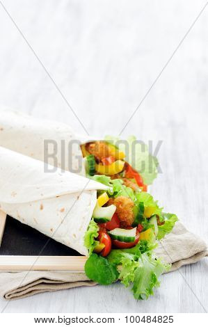 Crumbed chicken burrito lunch wrap with fresh healthy green salad, tomatoes, cucumber and bell peppers