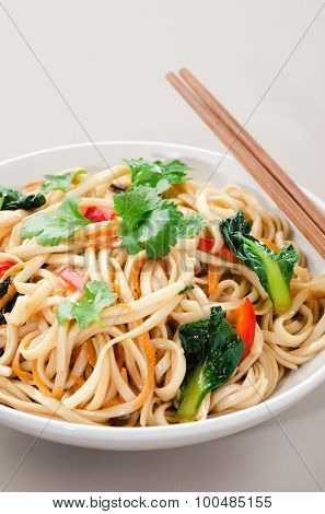 Chinese asian noodles stir fry with vegetables served with a pair of chopsticks