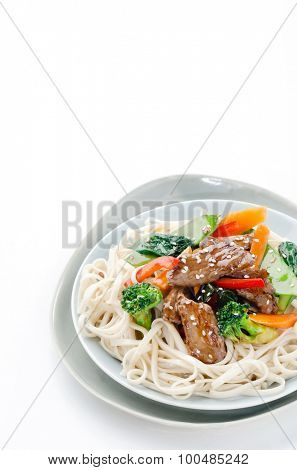 Beef stir-fry with broccoli, carrot, peppers, sesame seed on chinese noodles