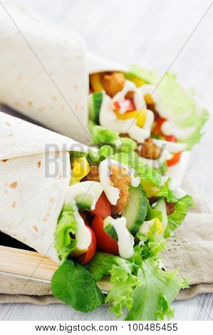 Light lunch chicken burrito wrap with fresh healthy green salad, tomatoes, cucumber, bell peppers and mayonnaise