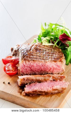 Grilled beef steak with fresh green salad on wooden board, a delicious healthy meal
