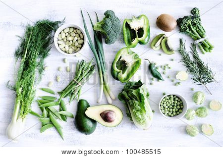 Collection of fresh green vegetables on white rustic background, broccoli, lettuce, celery, beans, capsicum, peppers, peas, brussels sprouts, kiwi, avocado,