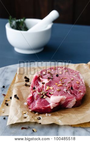 Beef steak on marble with herbs and spices