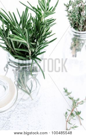 Fresh herbs in glass bottles, rosemary and thyme rustic farmstyle fresh clean and bright style