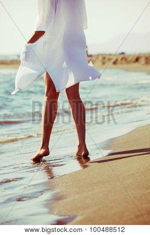 barefoot woman enjoy in sea water on sandy beach in white long shirt, lower body, back view