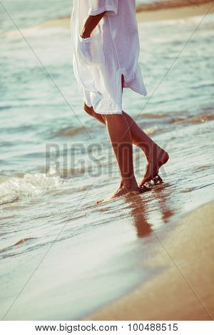 barefoot woman enjoy in sea water on sandy beach in white long shirt, lower body, side view
