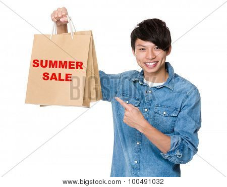 Man finger point to shopping bag for showing phrase of summer sale