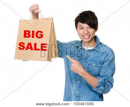 Man finger point to shopping bag for showing phrase of big sale