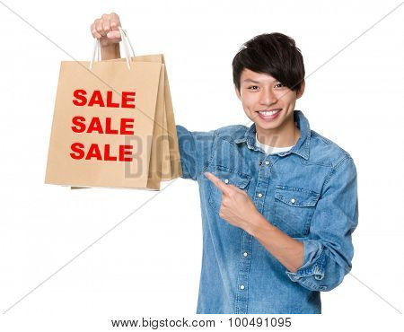 Man finger point to shopping bag for showing three words of sale