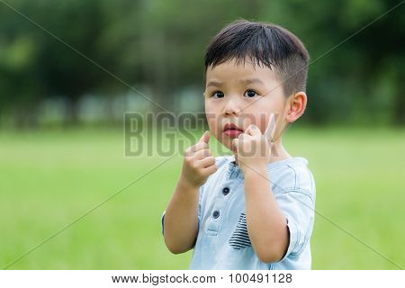 Lovely boy with finger on his face