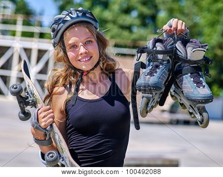 Girl holding  skate and roller skates in sport park