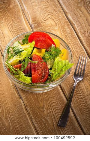 Salad with fresh vegetables, tomato and cucumbers