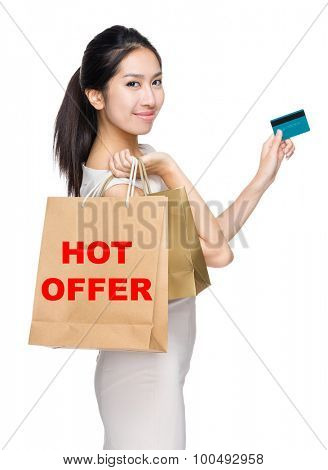 Woman with credit card and holding shopping bag for showing hot offer