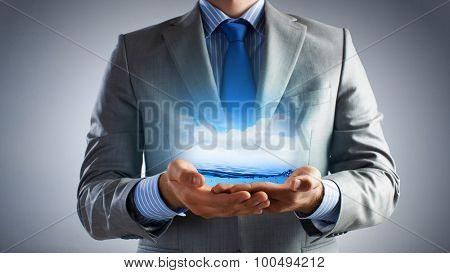 Close up of businessman holding clear blue water in palms