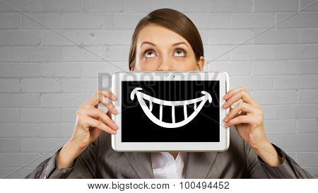 Beautiful young woman holding tablet with smile against her mouth