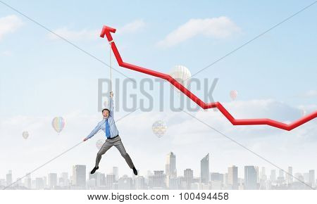 Young businessman hanging on increasing red graph