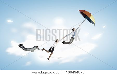 Business people flying in the sky on umbrella